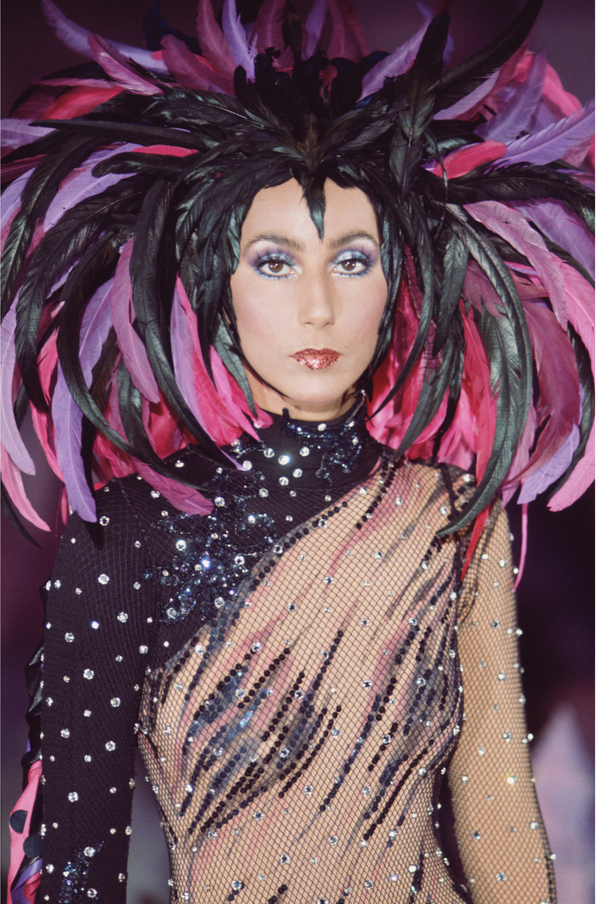 Promotional portrait of American singer and actress Cher (born Cherilyn Sarkisian LaPiere) in a semi-transparent outfit with a feathered headdress for the television variety show 'The Sonny and Cher Comedy Hour,' 1972. (Photo by CBS Photo Archive/Getty Images)